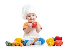 Baby wearing a chef hat with vegetables Royalty Free Stock Photos