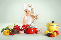Baby wearing a chef hat with vegetables and pan