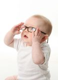 Baby wearing eyeglasses. Portrait of a baby wearing eyeglasses and playing with them Royalty Free Stock Photo