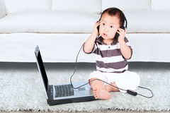 Baby wearing headset and using laptop Royalty Free Stock Images