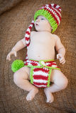 Baby Wearing Holiday Knitwear. Baby wearing red white and green striped knit hat and diaper cover Stock Images