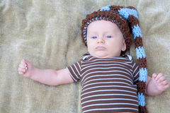 Baby Wearing Knit Hat Looking Up. Sweet baby boy wearing knit hat with brown and blue outfit lying on his back on a green blanket outside in the fall Royalty Free Stock Images