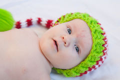 Baby Wearing Knit Hat. Baby wearing red white and green striped knit hat Royalty Free Stock Image