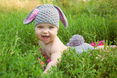 Baby wearing like a bunny or lamb. Portrait of baby wearing like a bunny or lamb of green grass. Happy childhood outdoors stock image