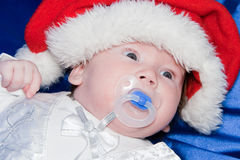 Baby wearing a red and white Christmas Santa hat. And with dummy in the mouth Royalty Free Stock Photos