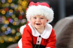 Baby wearing santa disguise looking at camera in christmas. Baby wearing santa claus disguise looking at camera in christmas on a couch in the living room at stock photo