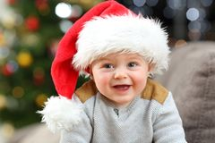 Baby wearing santa hat posing at home in christmas royalty free stock photo