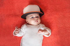 Baby wearing sport cap shows her tongue Stock Photo