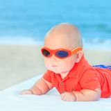 Baby wearing sunglasses. Cute baby wearing sunglasses on the sunbed Stock Image