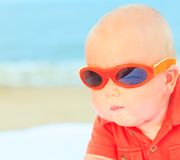 Baby wearing sunglasses. Cute baby wearing sunglasses on the sunbed Royalty Free Stock Photo