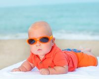 Baby wearing sunglasses. Cute baby wearing sunglasses on the sunbed Royalty Free Stock Photos