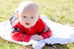 Baby Wearing Sweater Outside. Baby laying on stomach on a blanket outside on the grass Royalty Free Stock Photography