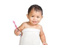 A baby wearing towel and holding a toothbrush. Stock Images