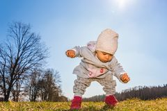 Baby wearing warm beanie hat, sweatshirt and red boots outdoors in rural area discovering nature in spring, sunny day. Baby wearing warm beanie hat, sweatshirt stock image