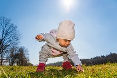 Baby wearing warm beanie hat, sweatshirt and red boots outdoors in rural area discovering nature in spring, sunny day