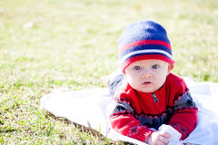 Baby Wearing Winter Clothes Outside. Baby laying on stomach on a blanket outside on the grass Stock Images