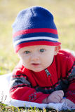 Baby Wearing Winter Hat and Sweater. A baby outside on a cold day wearing a knit winter beanie cap and red knit sweater Royalty Free Stock Image