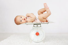 Baby on on weighing scale Royalty Free Stock Photos