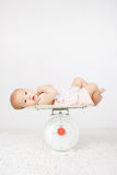 Baby on on weighing scale Stock Images