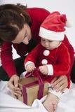 Baby Weihnachtsmann mit der Mutter, die goldenes Geschenk öffnet Lizenzfreie Stockfotos