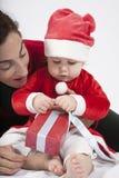 Baby Weihnachtsmann mit der Mutter, die rotes Geschenk öffnet Lizenzfreie Stockbilder