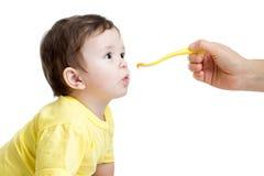 Baby, welches das Lebensmittel lokalisiert auf Weiß isst Lizenzfreie Stockfotos