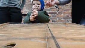 Baby, welches die Becken im Freien spielt Straßenmusiker stock video