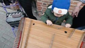 Baby, welches die Becken im Freien spielt Straßenmusiker stock video footage