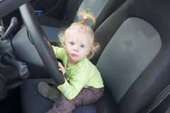 Baby at wheel. Baby blonde girl staring from the driving wheel in a car stock image