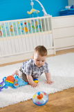 Baby and whirligig. Baby boy ( 1 year old ) sitting on floor at home and playing with whirligig Royalty Free Stock Photography