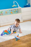 Baby and whirligig. Baby boy ( 1 year old ) sitting on floor at home and playing with whirligig Royalty Free Stock Photos