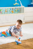 Baby and whirligig. Baby boy ( 1 year old ) sitting on floor at home and playing with whirligig Royalty Free Stock Image
