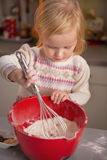 Baby whisking flour in kitchen Royalty Free Stock Photography