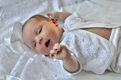 Baby in white clothes on a white background. A newborn is asleep, smiling. Small child royalty free stock image