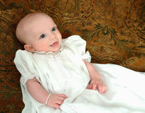 Baby in White Dress. Smiling baby girl in white dress on tapestry background Royalty Free Stock Photo