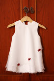 Baby white dress on hanger. Royalty Free Stock Photos