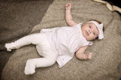 Baby in White Dress Laying on Gray Textile royalty free stock images
