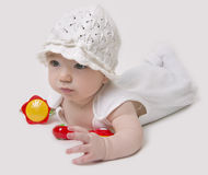 Baby in white hat playing with rattles. On white background Royalty Free Stock Photos