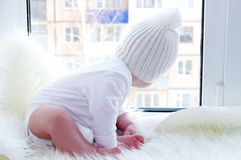 Baby in a white hat sits on a window sill Royalty Free Stock Image