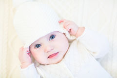 Baby in a white knitted sweater and hat on a white cable knit blanket Royalty Free Stock Photos