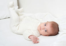 Baby on white towel in bed Stock Photography