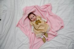 Baby in White and Yellow Dress on Pink Textile Stock Images