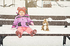 Baby on the winter bench with her toy Royalty Free Stock Images