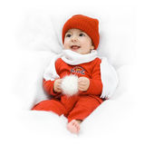 Baby in winter clothes. Happy baby wearing red winter clothes in a white blanket Stock Photo