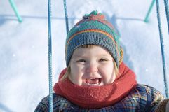 Baby in winter clothes playing on swing outdoor. happy smiling cute child in cap,scarf among the snow. Baby in winter clothes playing on swing outdoor. happy stock photography