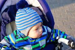 Baby in winter clothes. Sitting in buggy Royalty Free Stock Photos