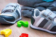 Baby winter clothing, concept, autumn, sneakers, caps, toys. how to dress baby in winter. choose the shoes. Stock Photo
