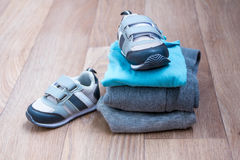 Baby winter clothing, concept, autumn, sneakers, caps, toys. how to dress baby in winter. choose the shoes. Royalty Free Stock Images