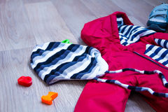 Baby winter clothing, concept, autumn, sneakers, caps, toys. how to dress baby in winter. choose the shoes. Stock Image