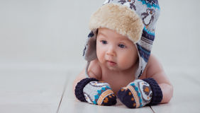 Baby in winter hat and mittens lying Royalty Free Stock Photos